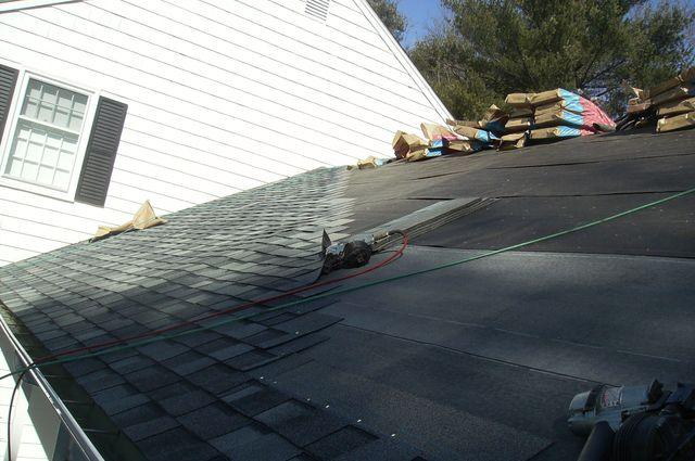 A close up on the new shingle roof mid-installation shows how the shingles are staggered, as well as the way they are nailed down to avoid seams from forming.