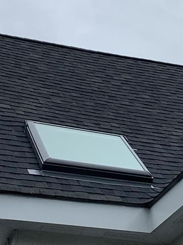 Exterior Roof work surrounding skylight including shingles and flashing.