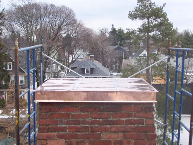 Our crew has finished this project, with the top of the chimney cap being installed. The copper makes the chimney cap look great, and the perfect seal around it along with the ice & water shield underneath will make sure that this chimney will not cause any more headaches for this happy homeowner.