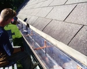 Man installing lead-coated copper gutters into shingle roof.