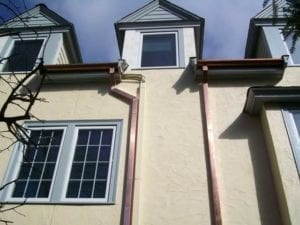 Copper downspouts installed by a roofing contractor in Newton, MA.