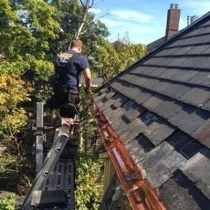Roofing contractor installing copper gutters into a slate roof on a home in Brookline, MA.