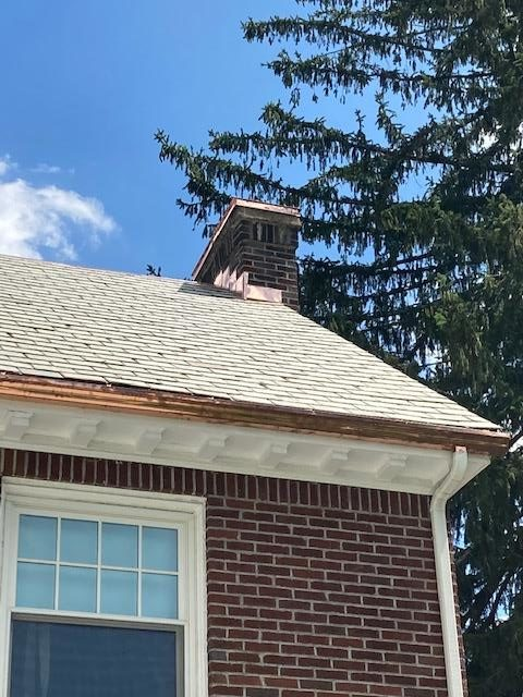 Installing brand new copper flashing onto this chimney on the home.