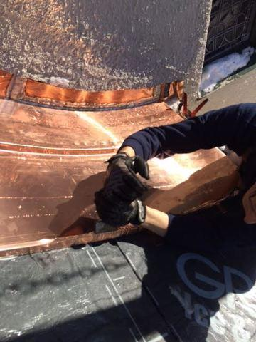 Here we can see one of our expert craftsmen putting the copper panels into place, making sure the curve fits properly against the shape of the roof. Ice & water shield is also applied to make sure water can't leak into the roof anymore.
