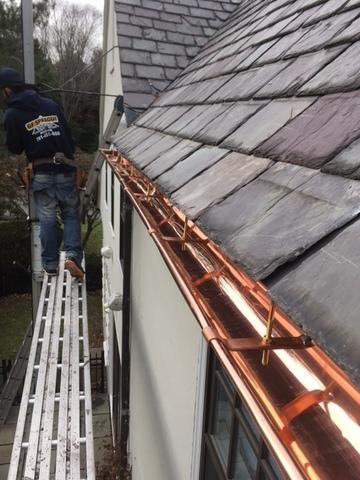 The copper gutters have been installed, and the slates run right up to the gutter line so water can easily run off the roof and into the gutters. These gutters will help rain and melted snow run down the gutters and downspouts rather than pouring right off the roof.