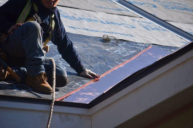 Installing asphalt shingles on top of ice and water shield.