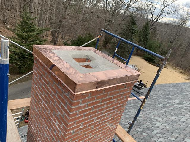 Installing a copper chimney cap onto the chimney.