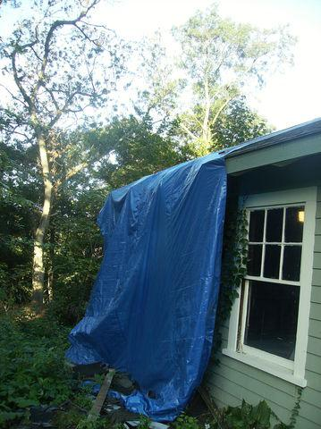 Our crew tarps off the roof to start, that way all of the removed shingles can be slid down the tarp and stay neat at the bottom of the tarp. This ensures that there is not debris all around the garage when the job is done.