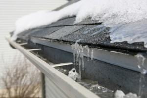 Ice dam on gutters and asphalt shingle roof.