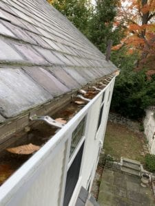 Leaves and flooding in clogged gutters.