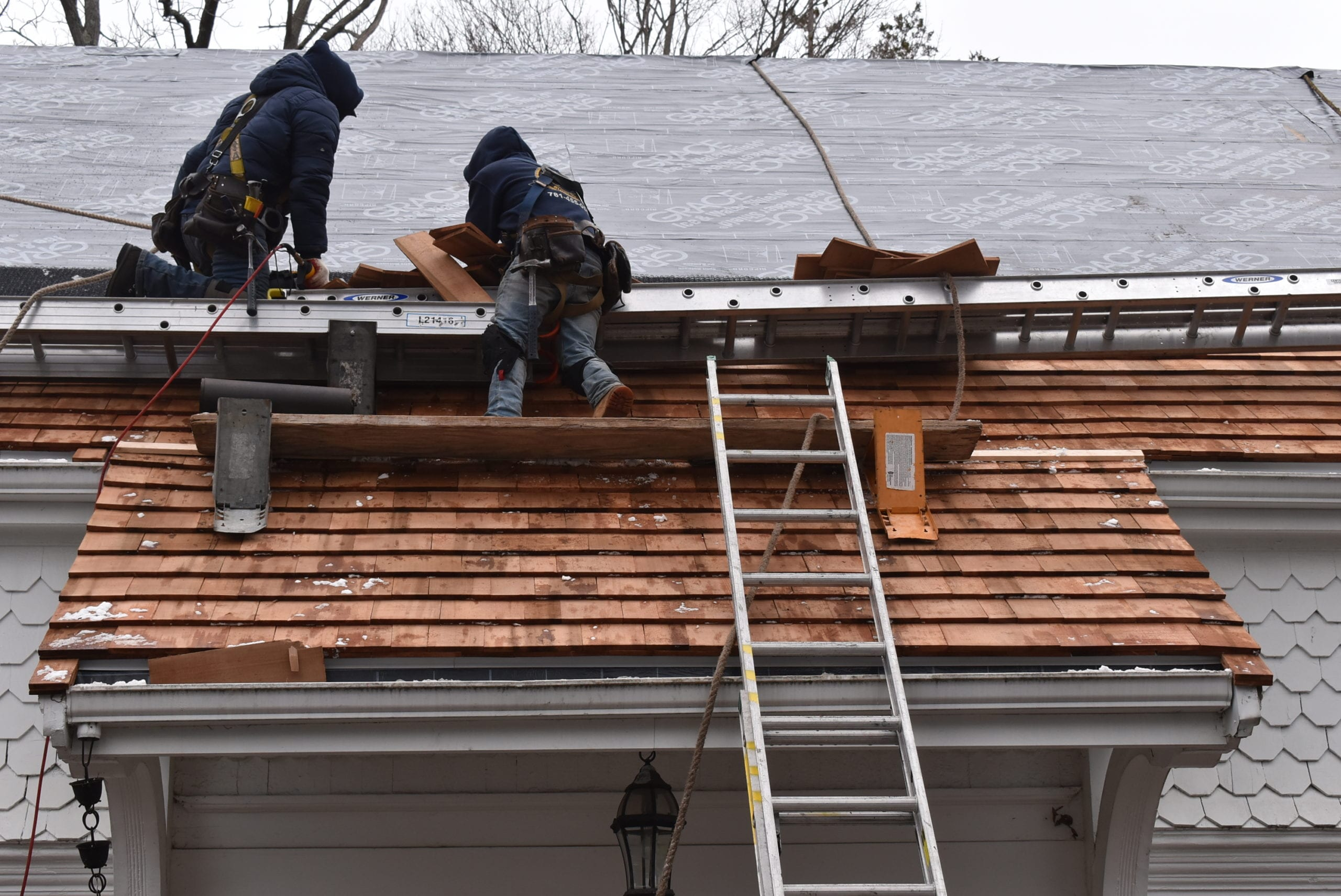 Our team installing cedar shakes onto a historic home in Milton, MA!